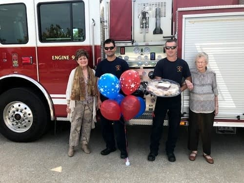 "Morning Pointe of Frankfort residents Pricilla Gersham (far left) and Thelma ""Pidgy"" Utz (far right) present firefighters Ken Blair and Matt Darst (center) with a gift basket of homemade goodies to thank them for their service."