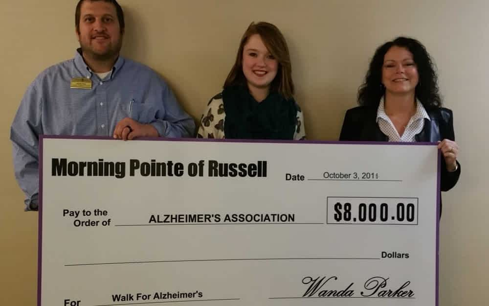 Morning Pointe of Russell associates Charlie Pack, Lantern program director, and Wanda Parker, senior executive director, present a check valued at $8,000 to Alex Russell (center) with the Alzheimer's Association.