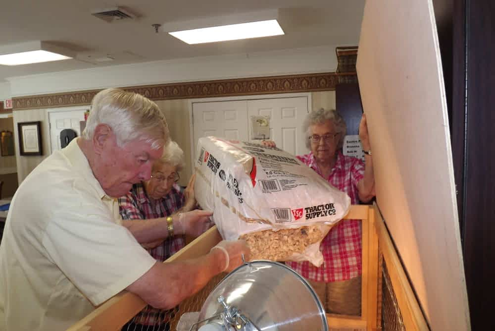 Max Eubanks, Blanche Eilert and Donna King, Morning Pointe of Franklin residents, love to lend a helping hand tending to our chickens. Their bedding is changed on a regular basis as well as the water and food.