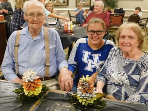 James and Betty Ramey, Morning Pointe of Danville residents, show off their painted pine cones with Samantha Yontz from the Bethel Baptist Church group 'Girls in Action.'