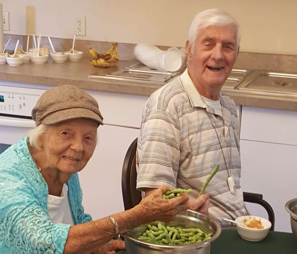 David Phelps and Betty Cleary, Morning Pointe of Russell residents enjoyed string beans from the local farmer's market.